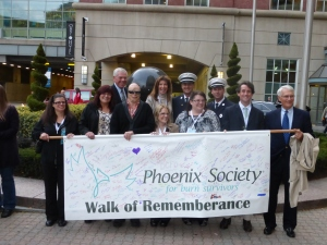 Phoenix Society's members and special guests carry the Walk of Remembrance banner